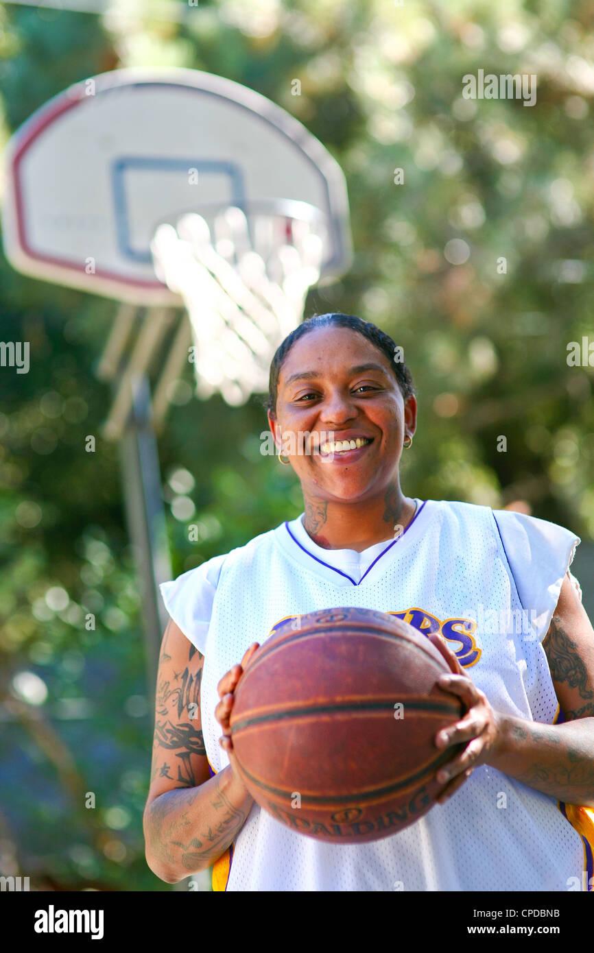 Une jeune femme afro-américaine avec des tatouages sourit, tenant un basket-ball en face d'un panier de Photo Stock
