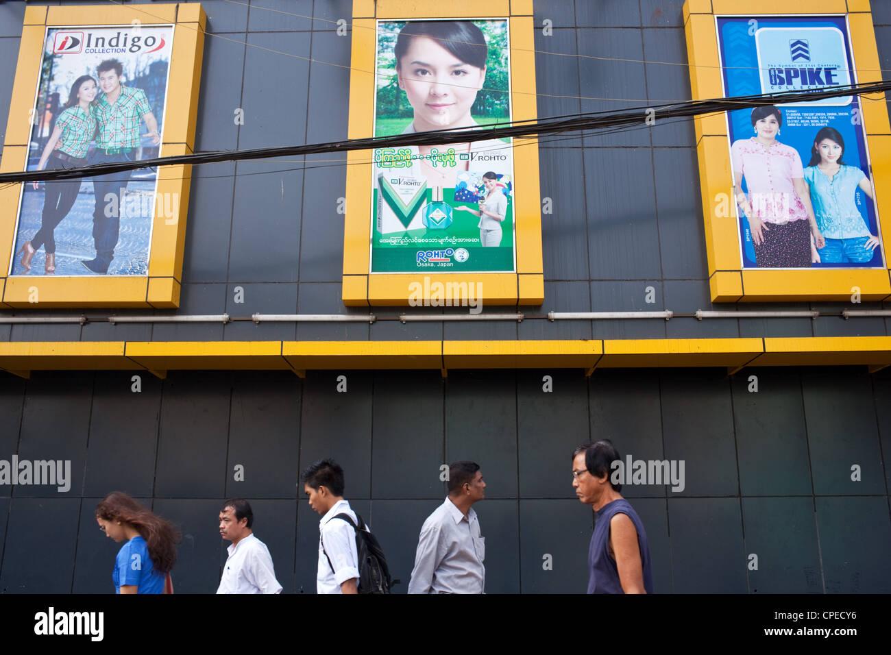 Birmans marcher sous vêtements publicitaires affiches dans le centre de Yangon (Rangoon), le Myanmar (Birmanie) Banque D'Images