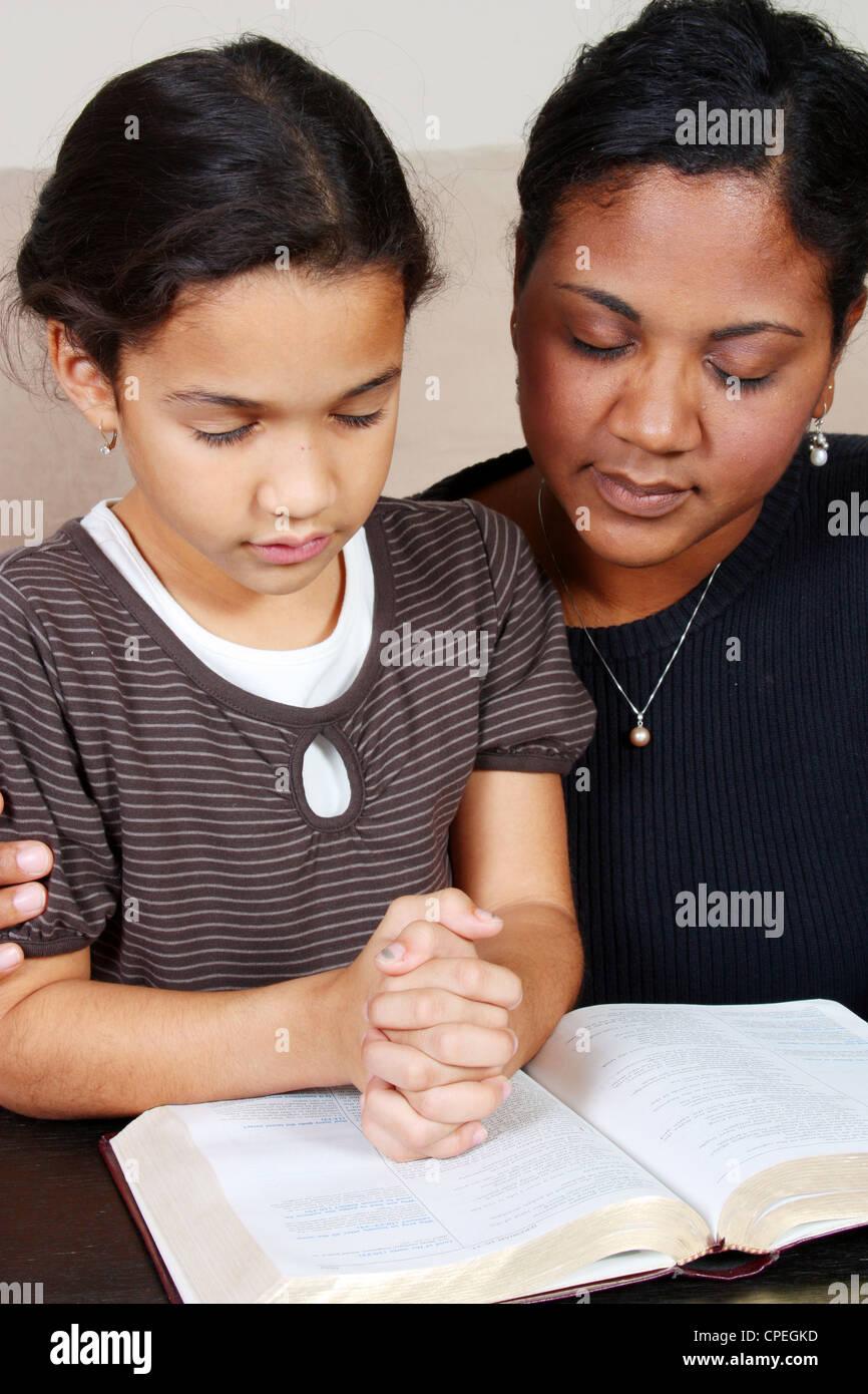 Femme de la minorité et sa fille priant ensemble Photo Stock