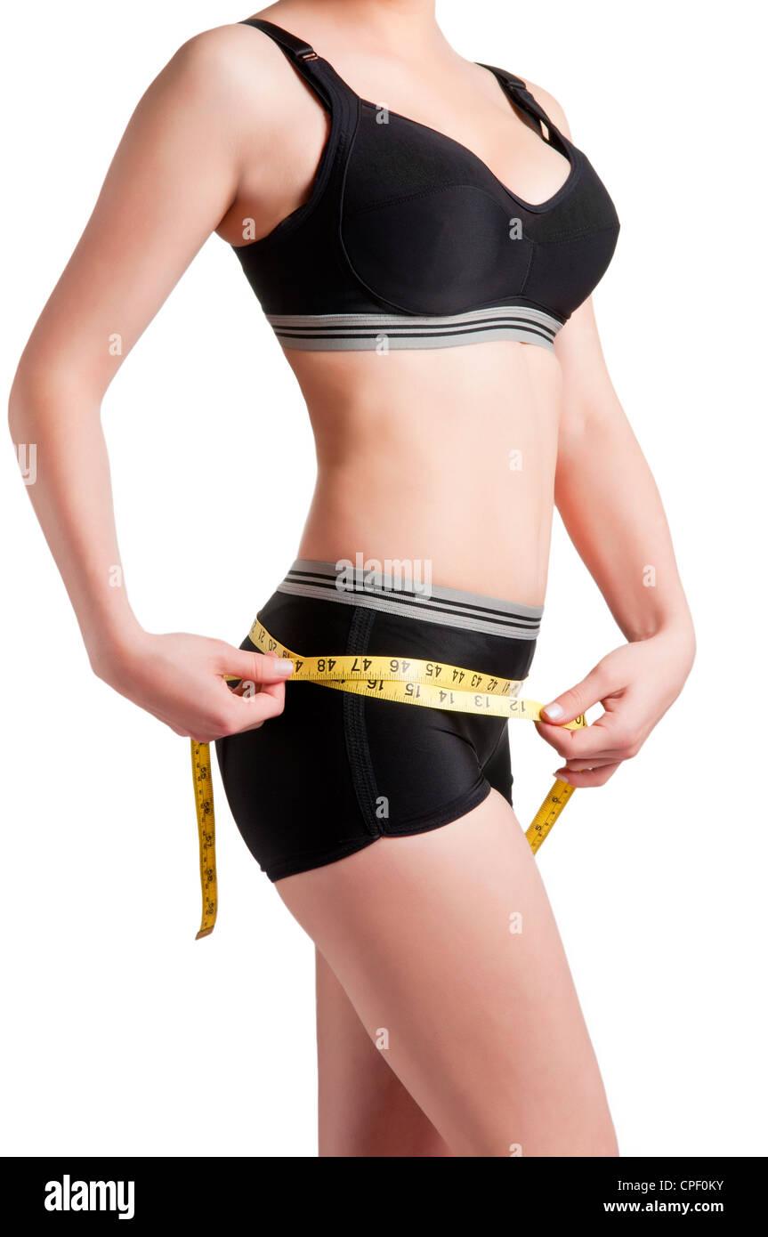 Woman measuring her waist jaune avec un ruban à mesurer Photo Stock