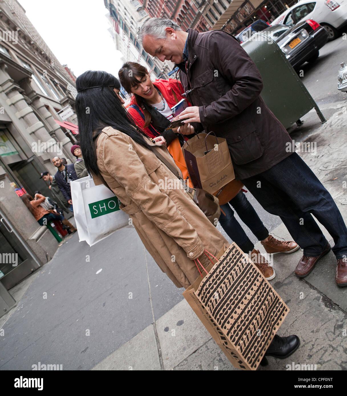 Un homme montre ses compagnons ses achats dans la ville de New York. Photo Stock
