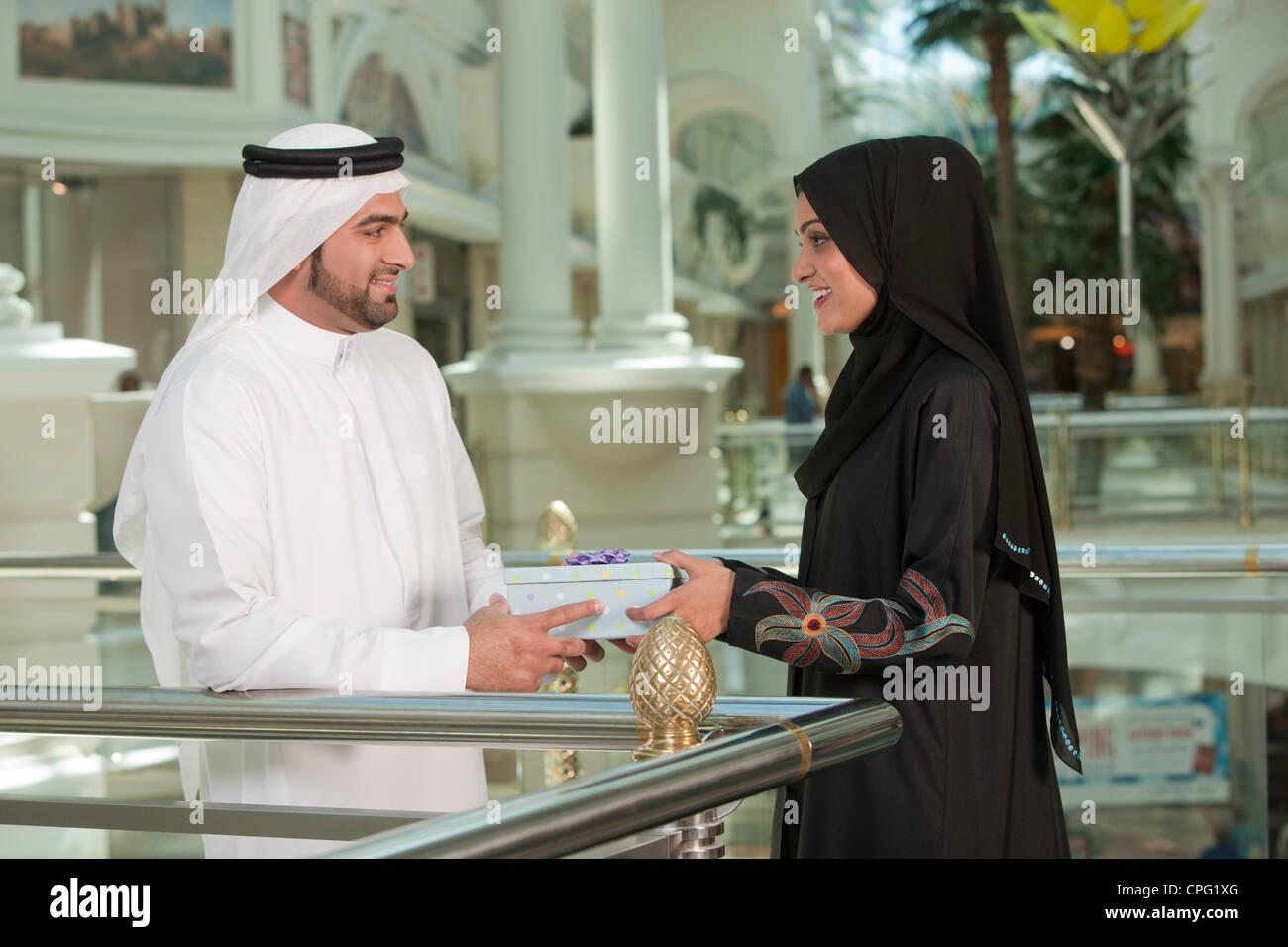 L'homme arabe cadeau donnant à la femme. Photo Stock
