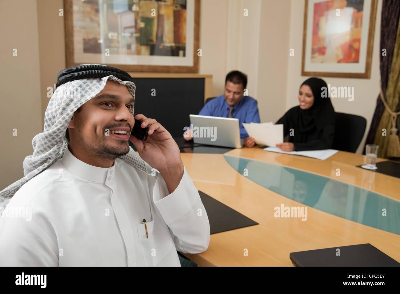 Businessman using mobile phone, deux collègues en arrière-plan. Banque D'Images