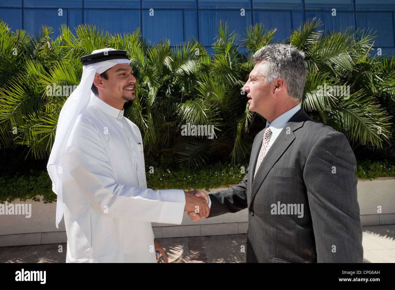 Homme d'arabe et de l'ouest businessman shaking hands in front of office building. Photo Stock