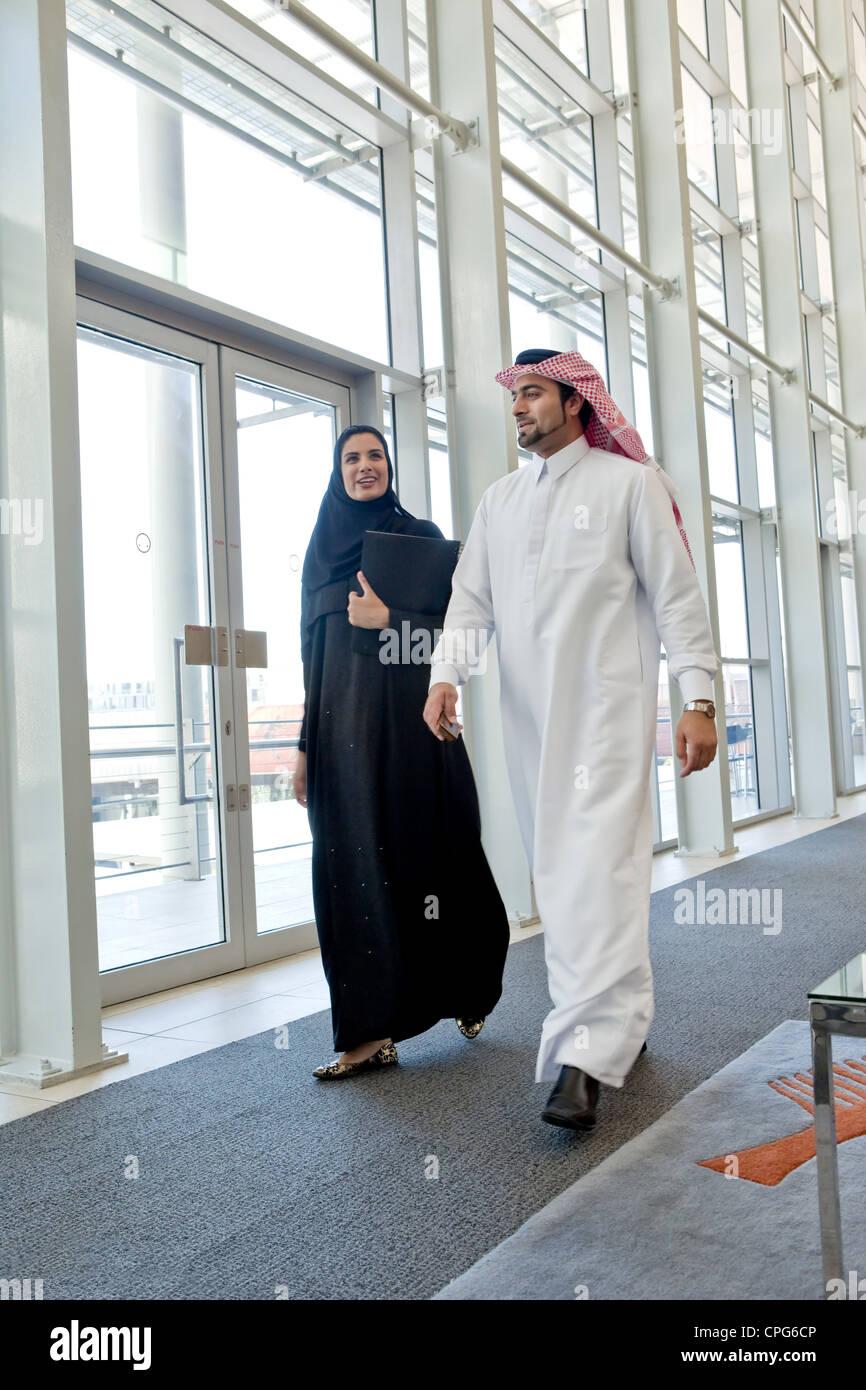 Businessman and businesswoman arabes à parler tout en marchant dans le couloir. bureau Photo Stock