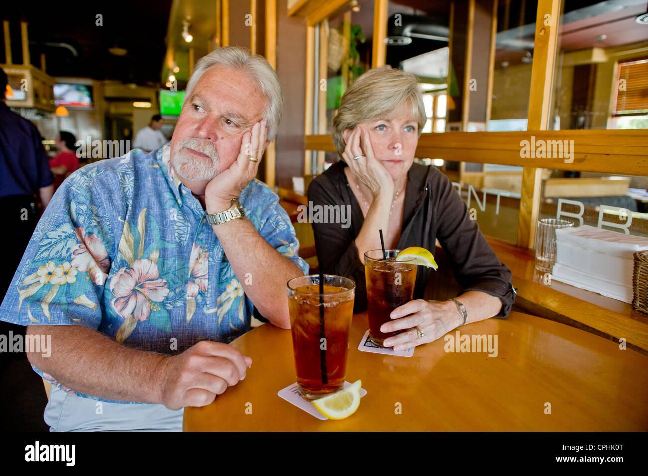 Un couple d'âge moyen semblait indifférent à l'ensemble plus de thés ensemble dans un Long Beach, CA, restaurant Banque D'Images