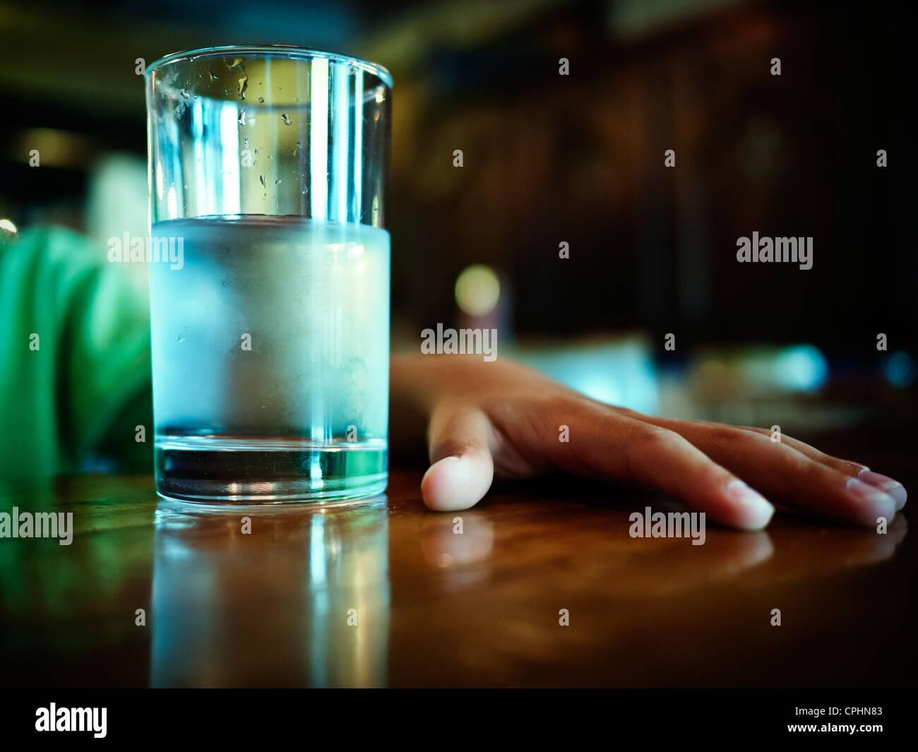 Verre d'eau glacée et main sur la table Photo Stock