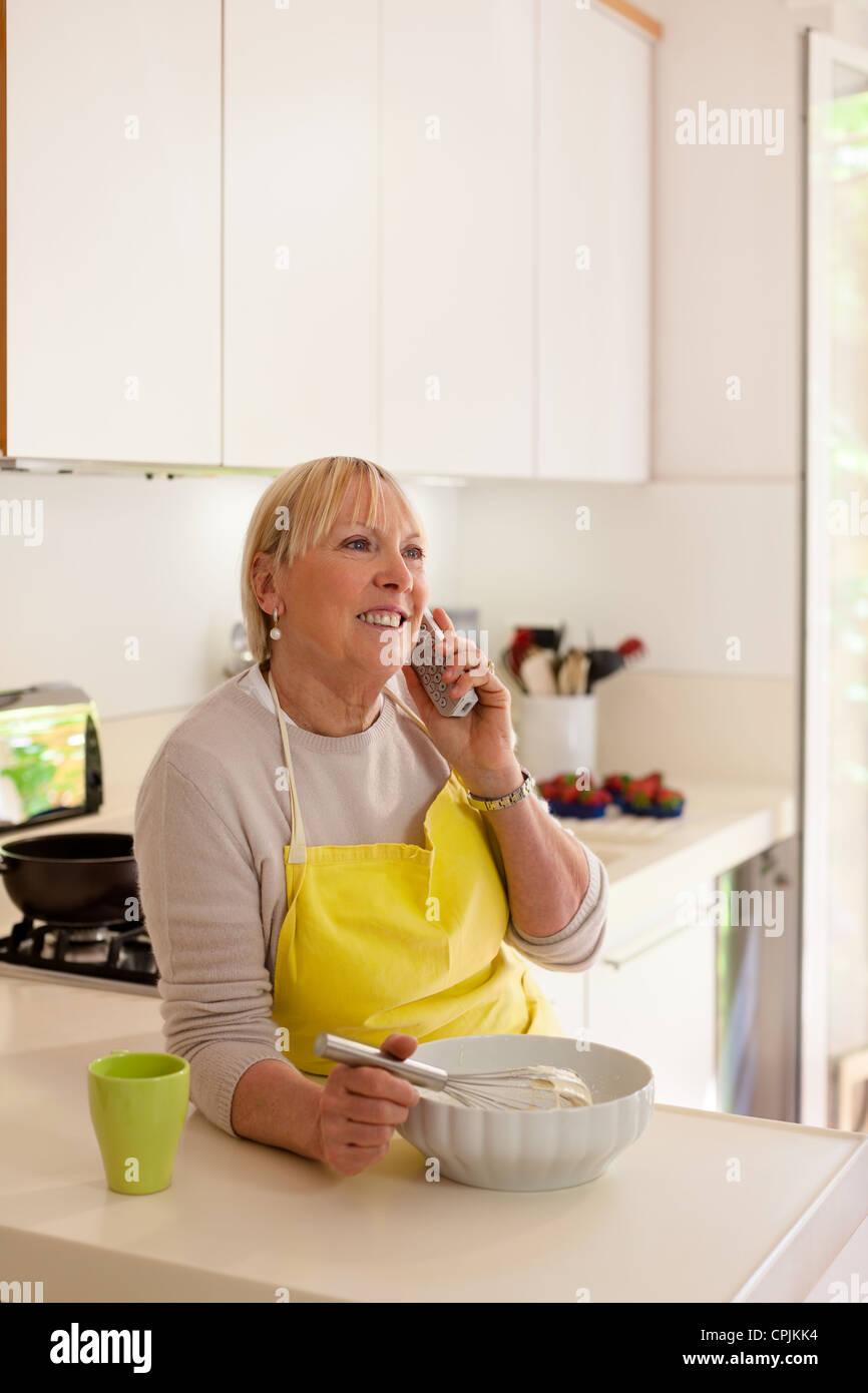 Happy senior woman at home, la cuisson dans la cuisine et parler au téléphone Photo Stock