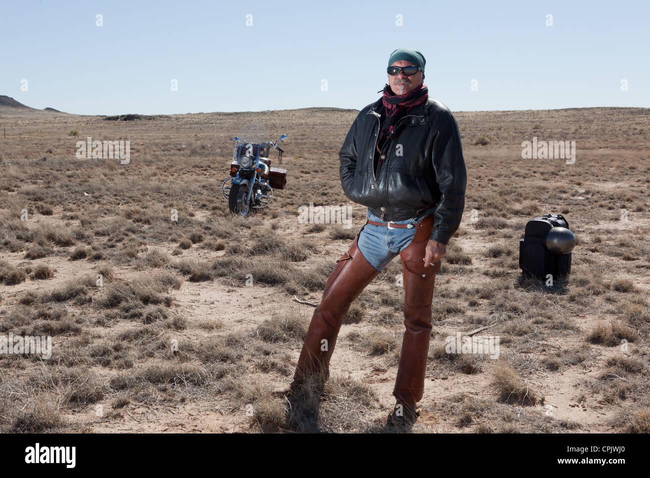 1d1332f81cb0d0 Homme plus âgé, portant des lunettes et une veste en cuir chaps debout au  milieu du désert avec sa moto et pack.