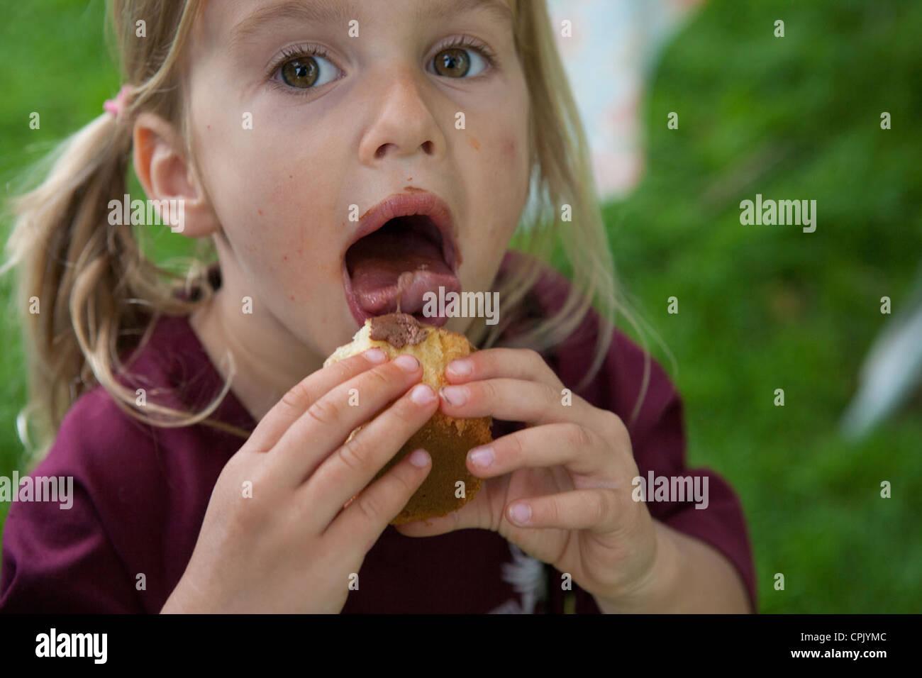 Quatre ans, fille de lécher le glaçage d'un cupcake. Banque D'Images