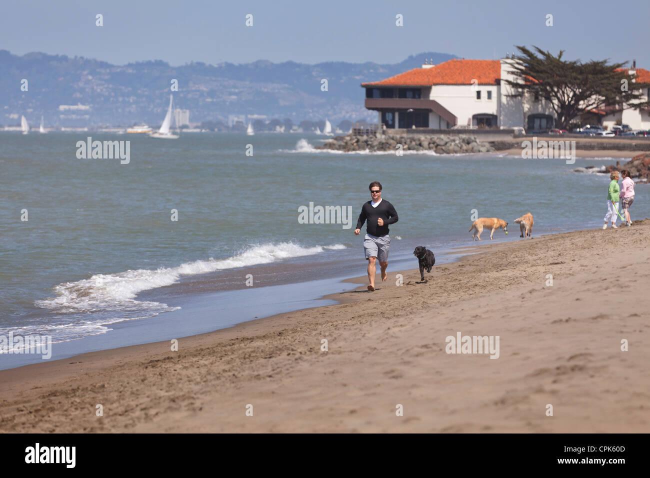 Un homme qui court sur la plage avec un chien Banque D'Images