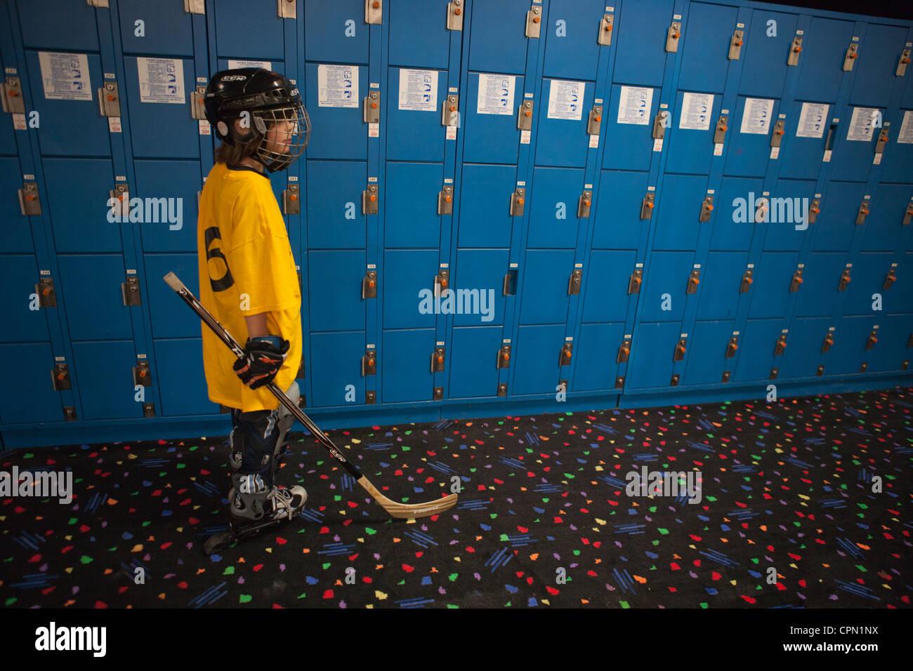 Neuf ans habillé pour roller hockey debout devant un mur de casiers bleus. Photo Stock