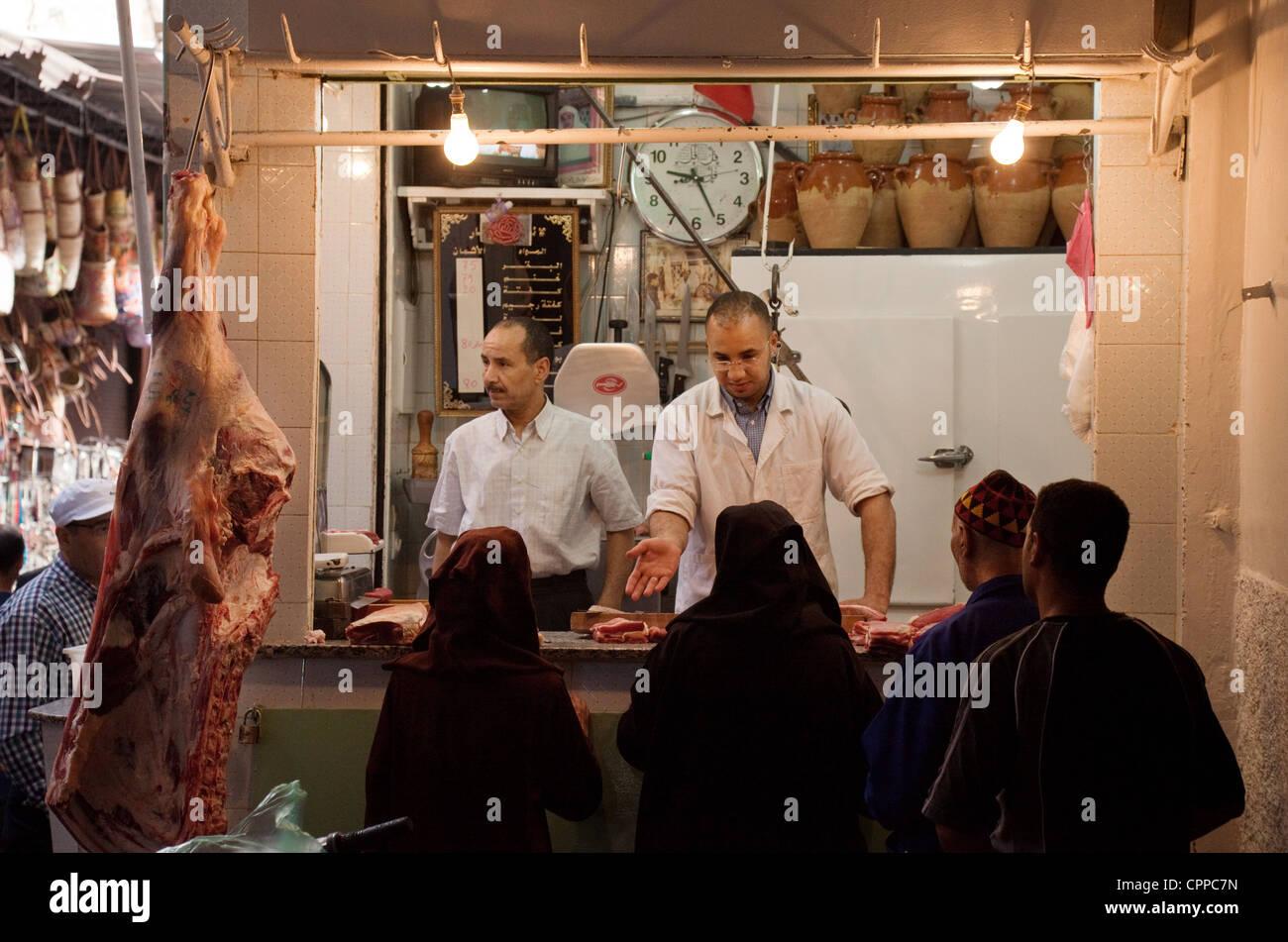 La population locale d'acheter la viande dans le marché (souk), Marrakech, Maroc, Afrique du Sud Banque D'Images