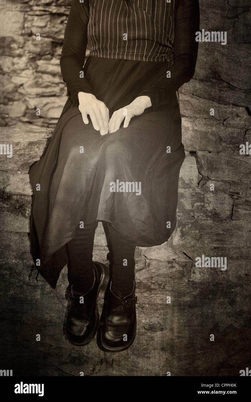 Une femme assise sur un vieux mur de pierre dans la région de old-fashioned vintage dress Photo Stock