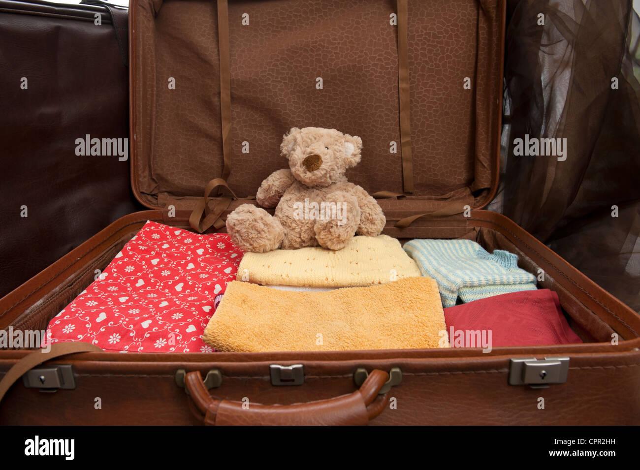 Valise ouverte avec des vêtements et ours Photo Stock