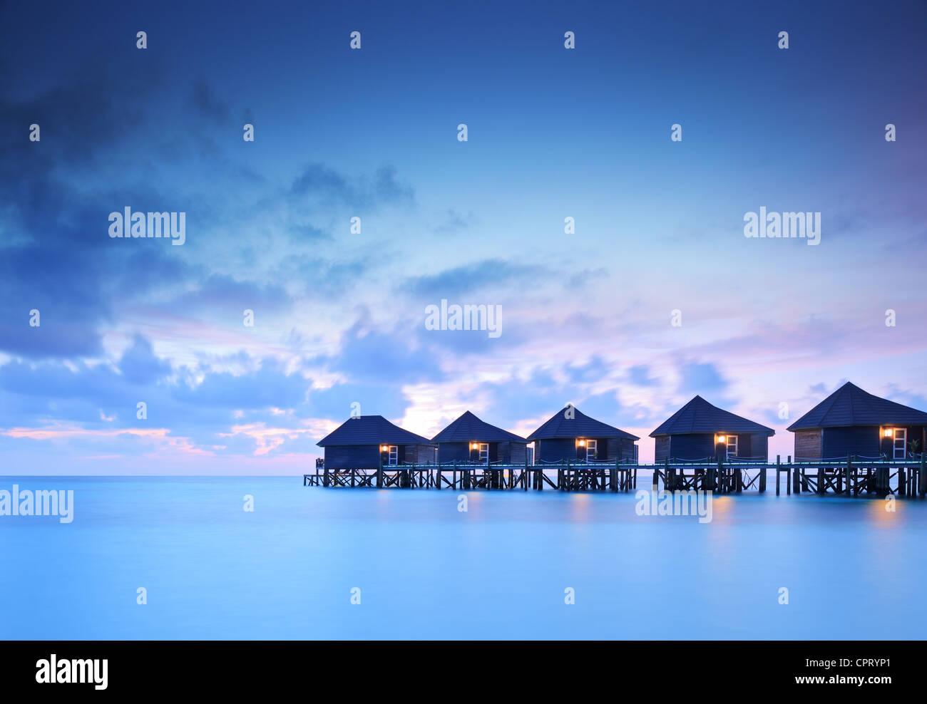 Water villa cottages au coucher du soleil sur l'île de Kuredu, Maldives, Lhaviyani atoll Photo Stock