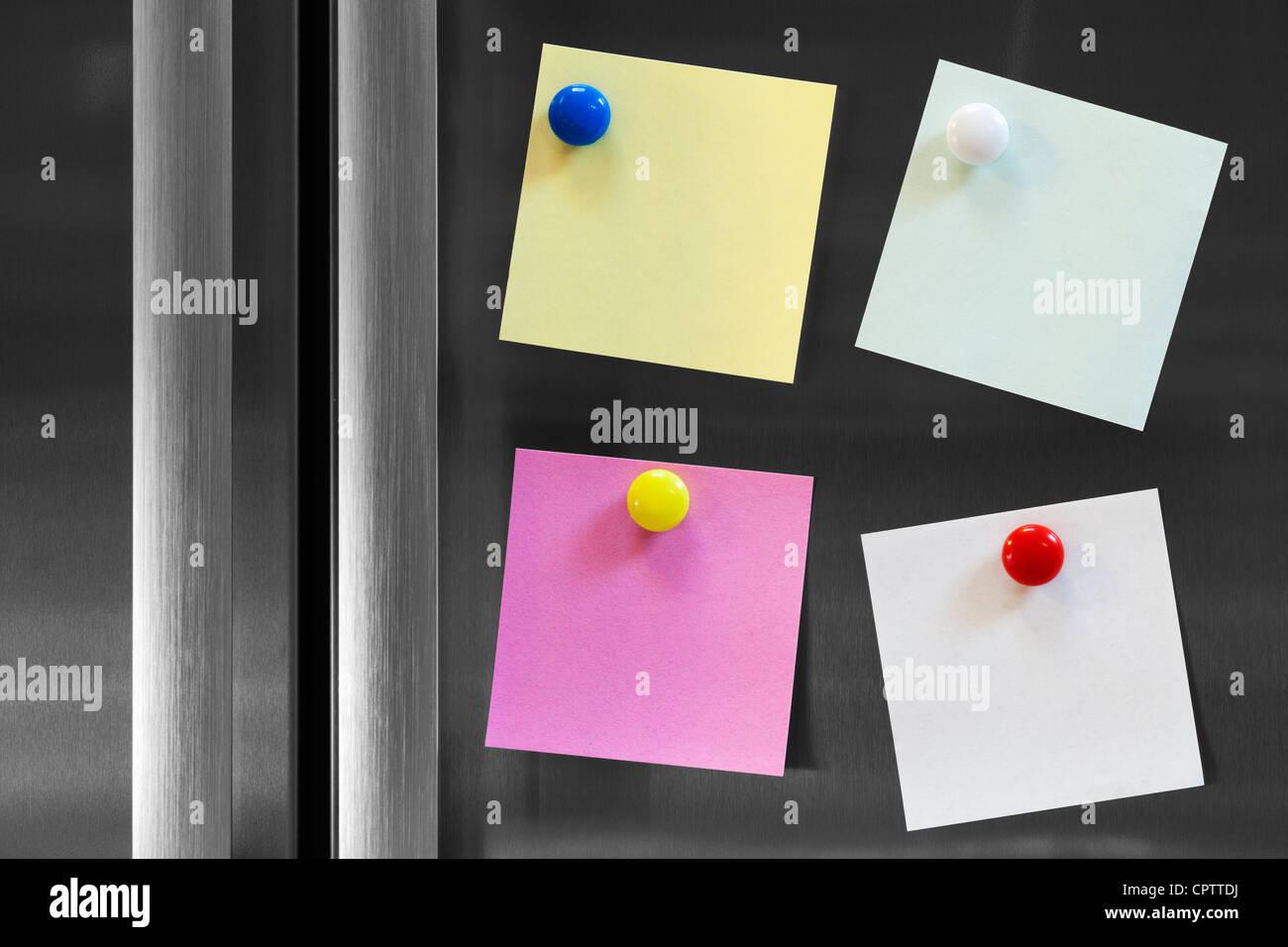 Quatre notes colorées attachées à un réfrigérateur avec des aimants de réfrigérateur, Photo Stock