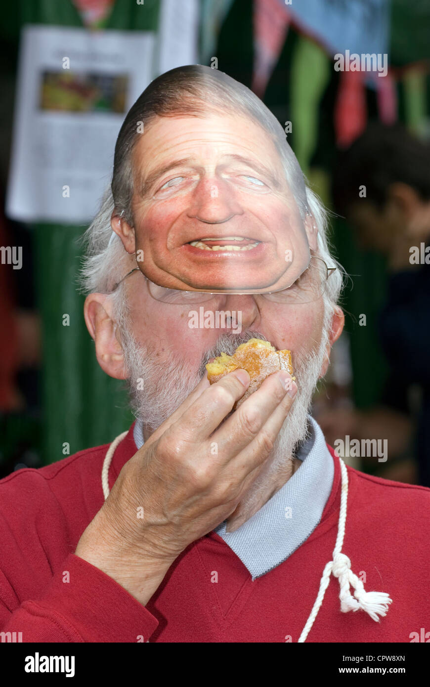 Un homme âgé portant un masque de Prince Charles et manger une collation au Dockenfield fete & Diamond Photo Stock