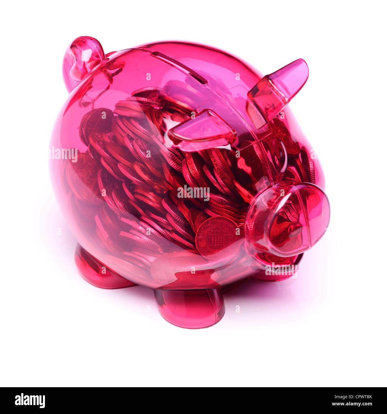 En plastique rose transparent tirelire pleine de coins Photo Stock