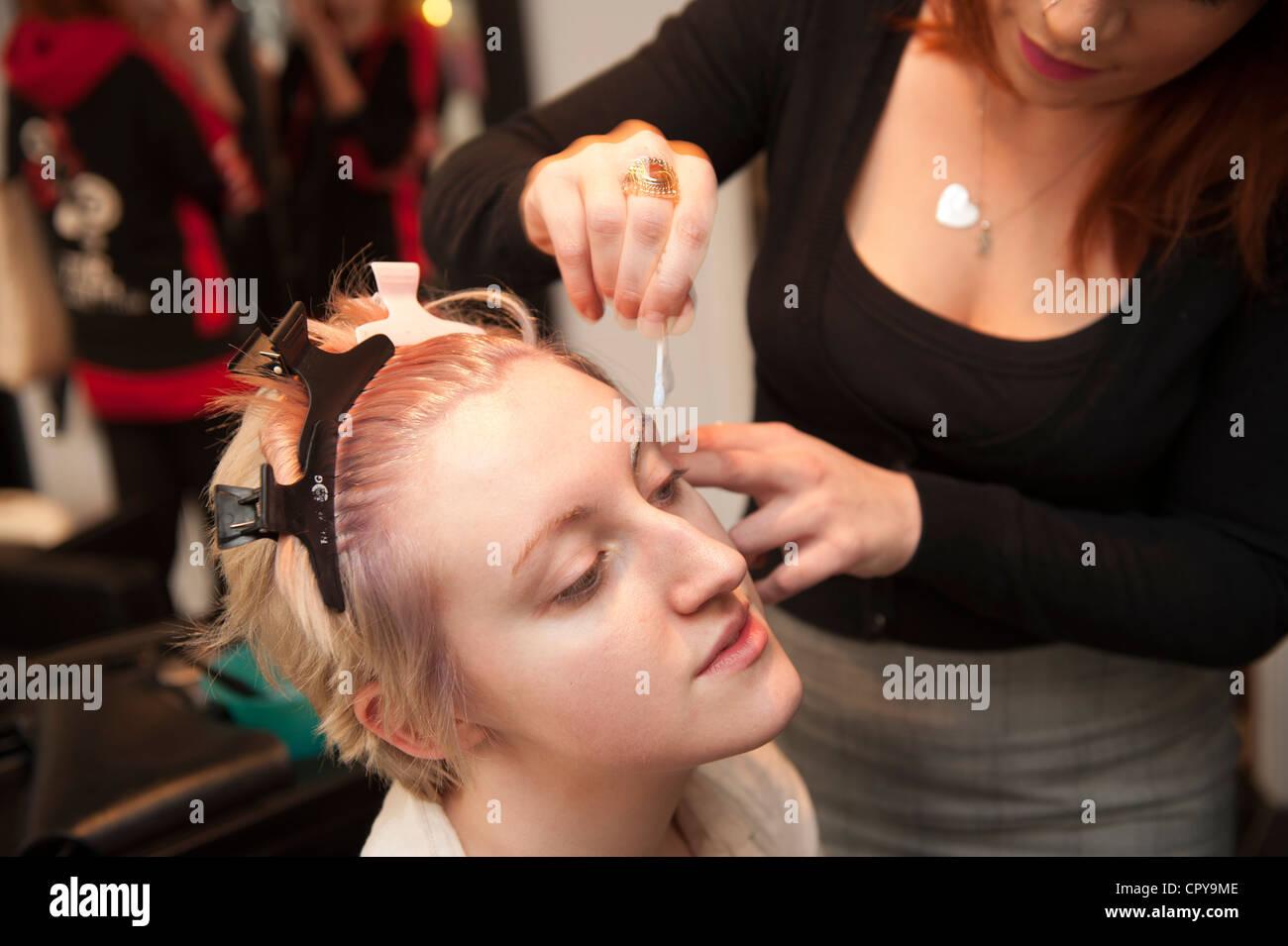 Une jeune femme ayant un cheveux et maquillage beauté make-over dans un salon, blanchiment ses sourcils, UK Banque D'Images
