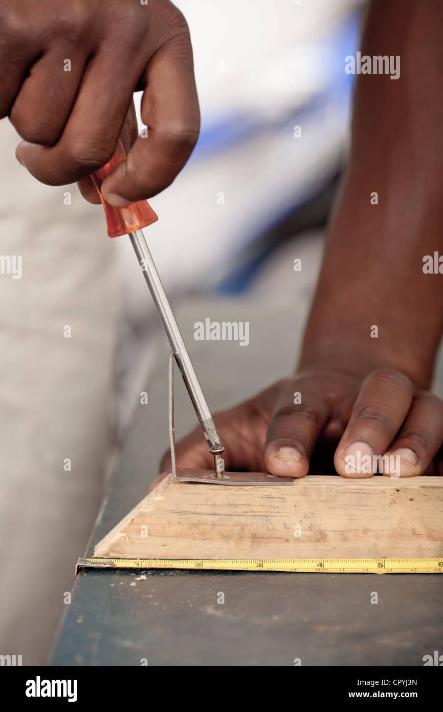 Libre d'un Africain mans mains vissage d'une vis dans un morceau de bois Photo Stock