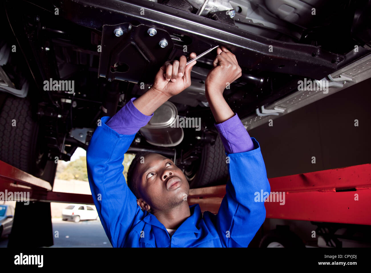 Mécanicien d'Afrique sous une voiture, travaillant sur le moteur Photo Stock