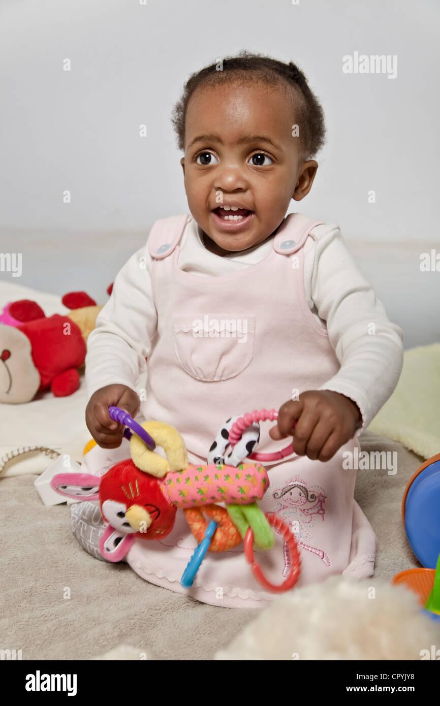 Femelle noire bébé jouant avec des jouets Photo Stock