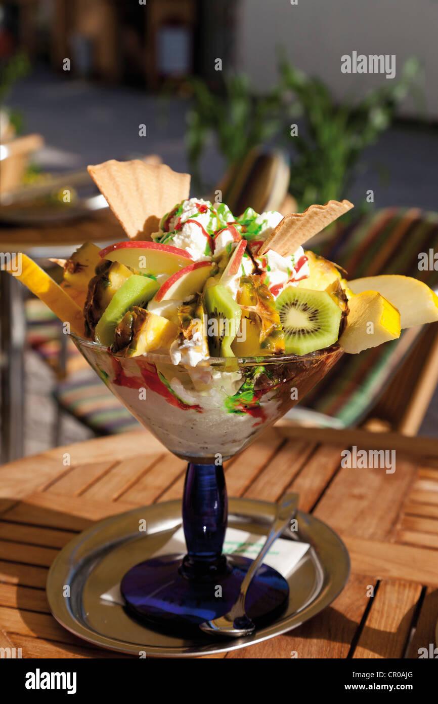 Bol de crème glacée avec un mélange de fruits et crème fouettée Photo Stock