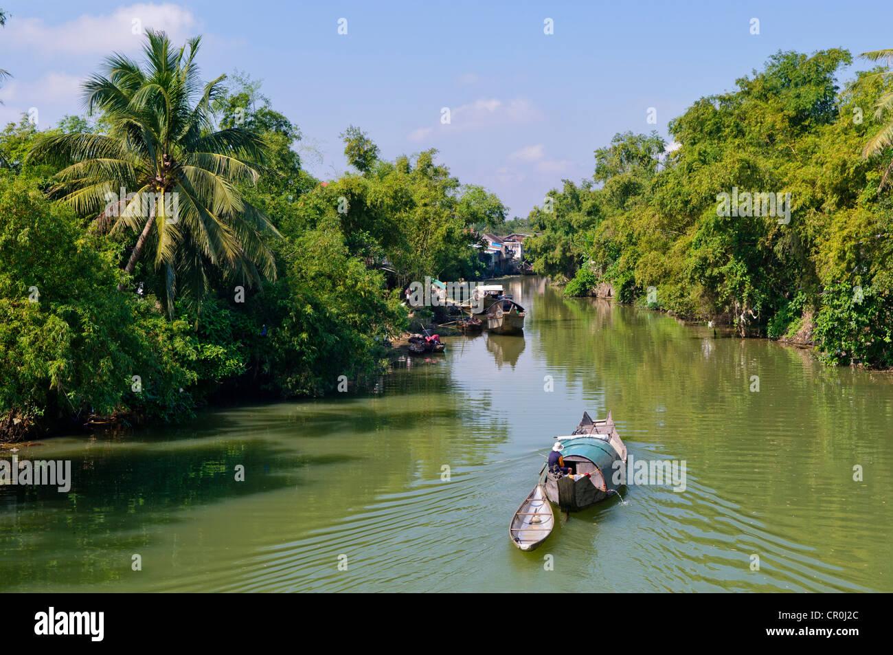 Petit bateau à moteur en passant par un canal d'eau entourée de végétation tropicale, Hue, Photo Stock