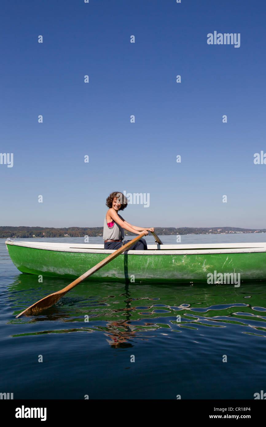 Woman rowing boat dans le lac encore Photo Stock
