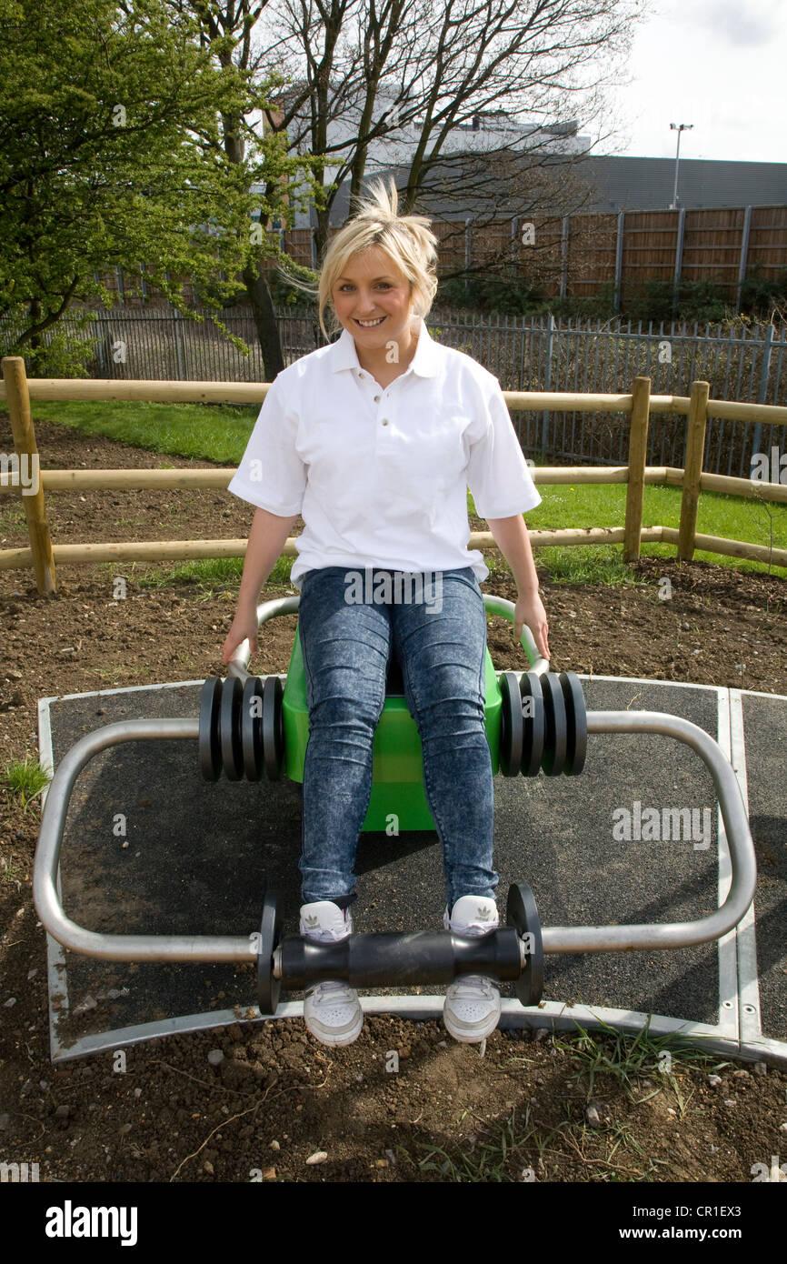 Fille sur la machine d'exercice en plein air Photo Stock