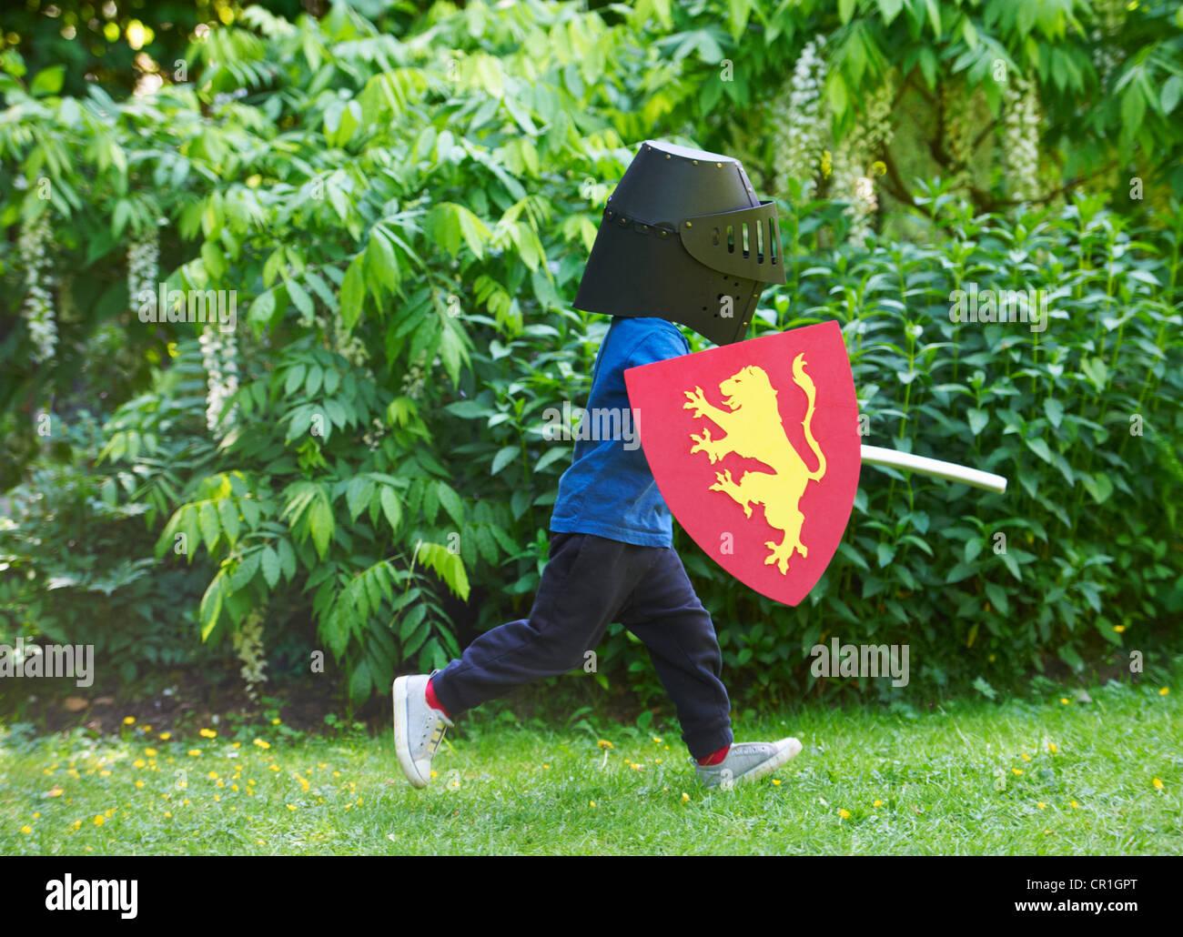 Garçon jouant avec sword in backyard Photo Stock