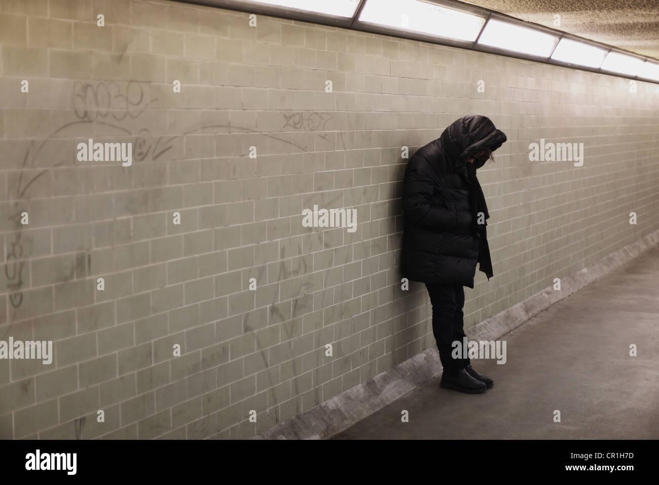 Personne à capuchon s'appuyant sur le mur du métro Photo Stock