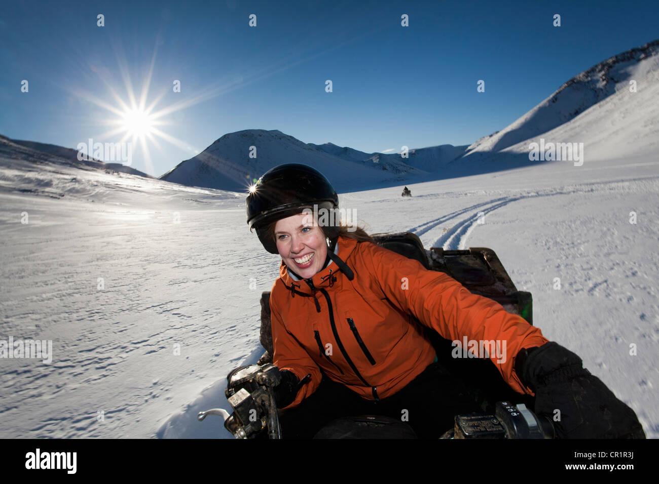 Woman driving motoneige en champ neigeux Banque D'Images