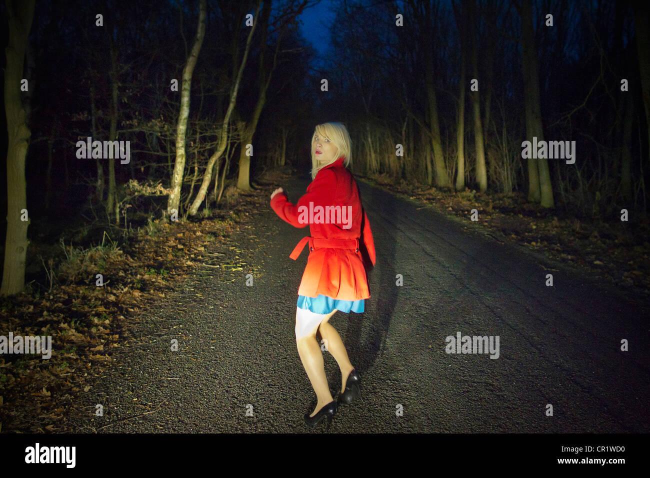 Femme tournant dans la peur dans les bois La nuit Photo Stock