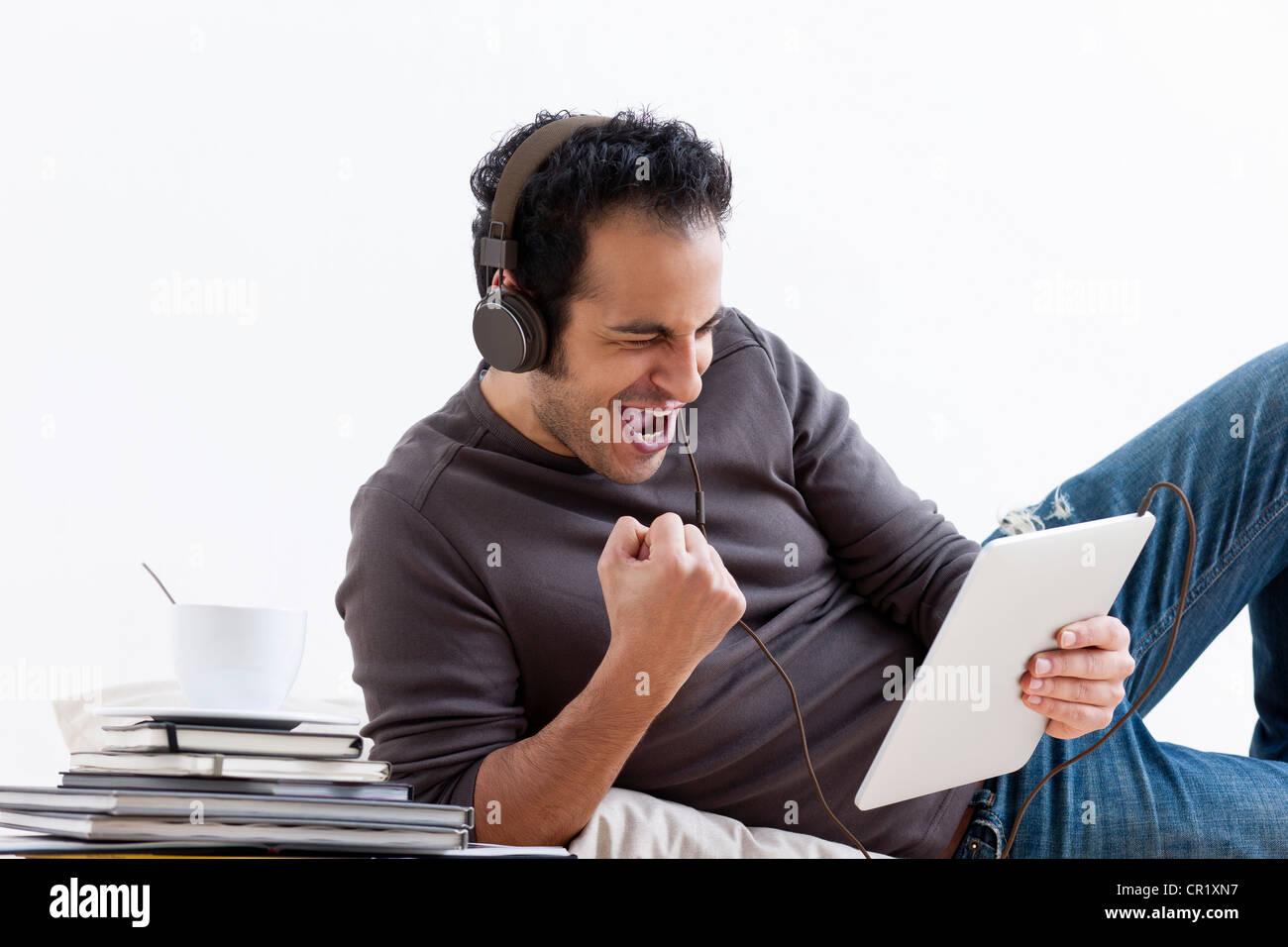 L'homme à l'écoute de tablet computer Photo Stock