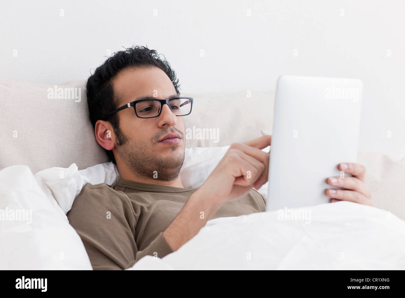 Man using tablet computer in bed Photo Stock