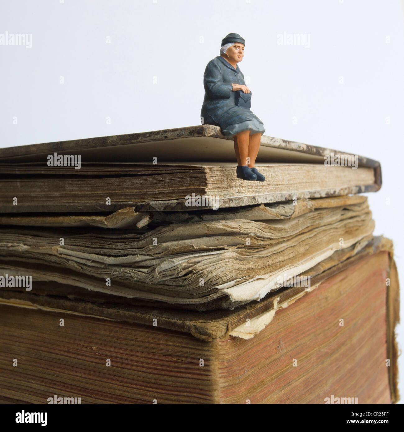 Dame âgée, miniature, figurine, assis sur un vieux livre - connaissance / sagesse / concept histoire de Photo Stock
