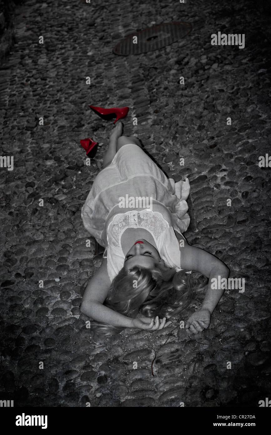Jeune femme allongée sur la rue sur un cobblestone dans une robe blanche avec des pompes rouge Photo Stock