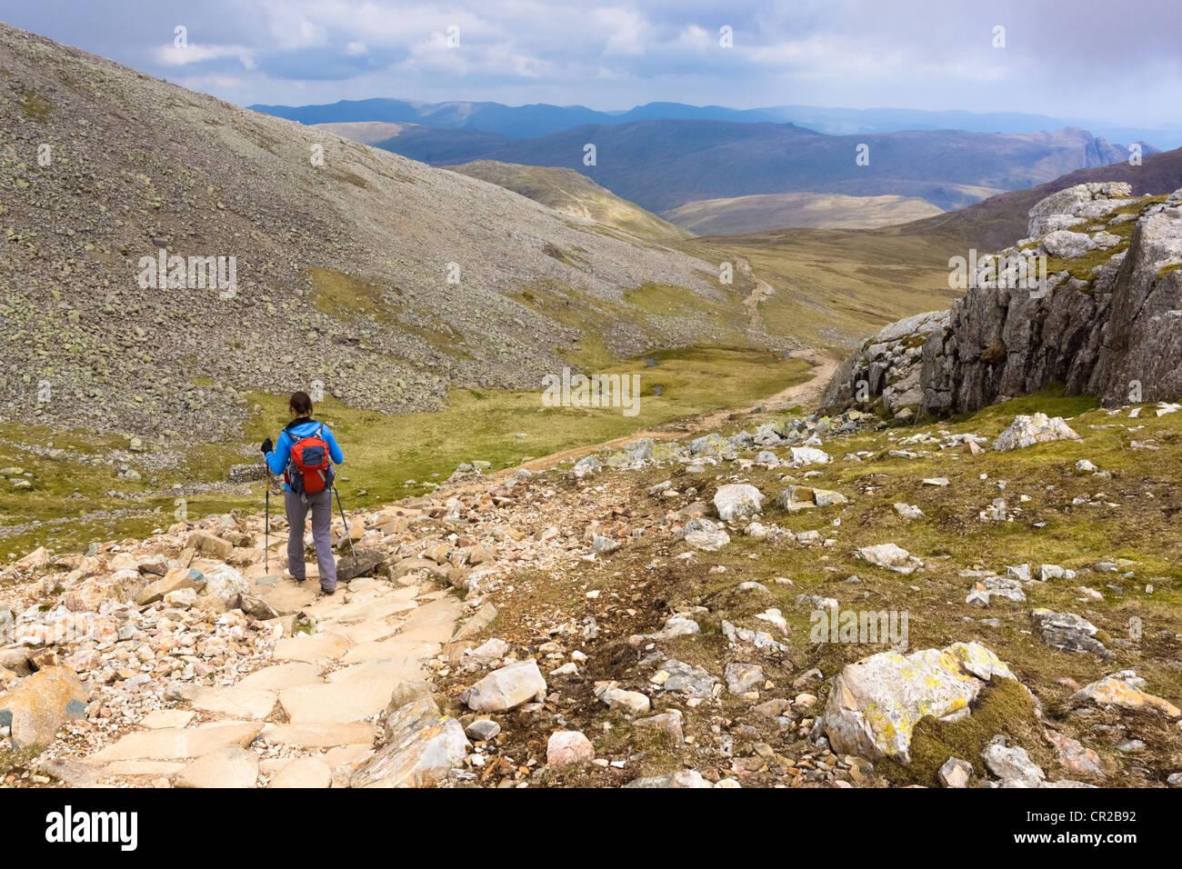 Un randonneur descend le chemin escarpé des sommets de mauvais et Broad Crag dans le Lake District. Le Langdale Pikes peut être vu dans le Banque D'Images