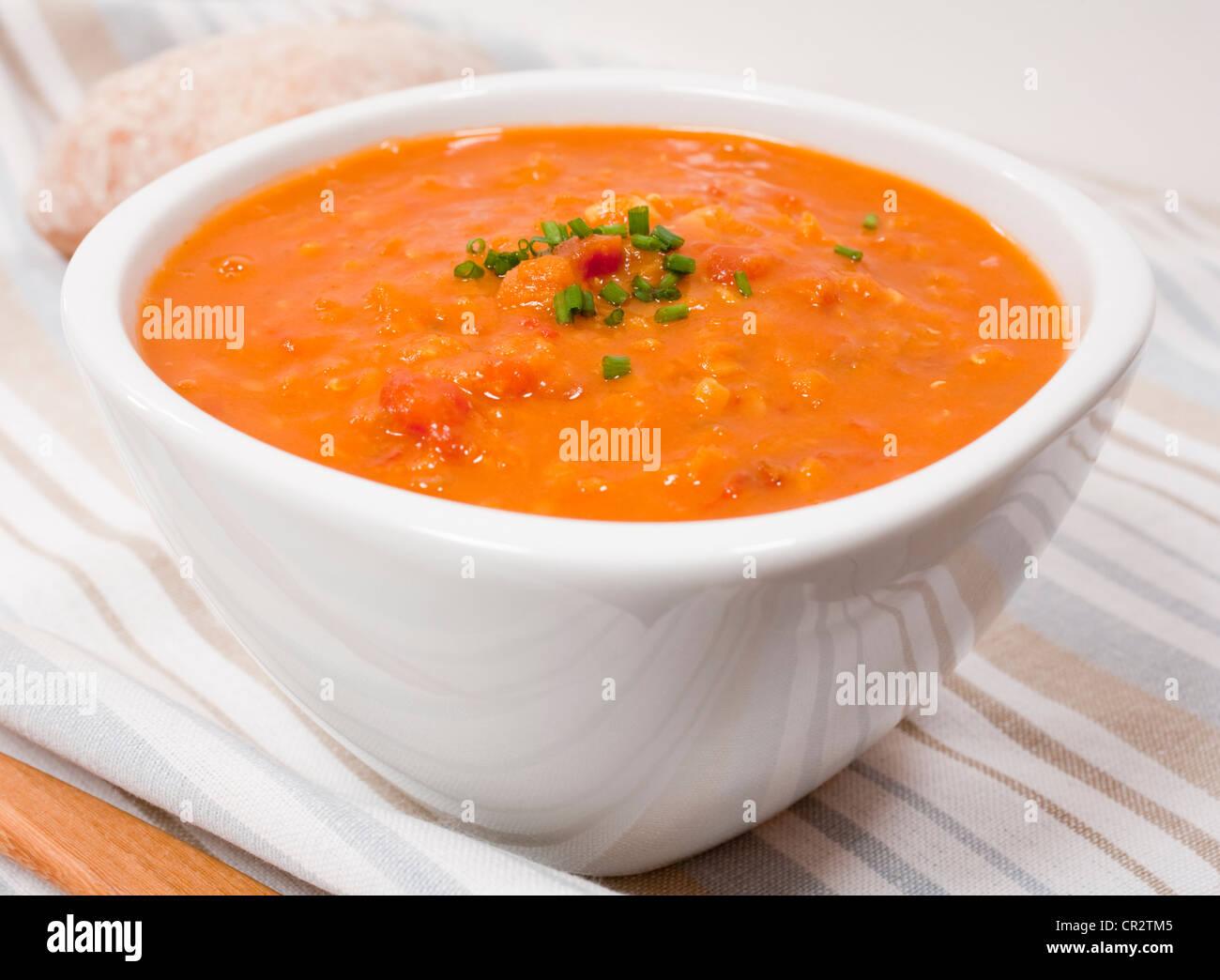 Un bol de soupe aux tomates et lentilles garnie avec de la ciboulette. Photo Stock