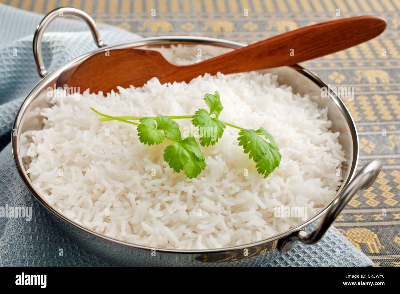 Le riz Basmati dans un steel karahi, garni de coriandre,avec une cuillère en bois. Photo Stock