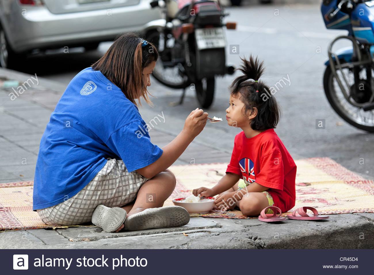 Mère nourrit sa fille sur le bord de la route, Bangkok, Thailande, Asie Banque D'Images