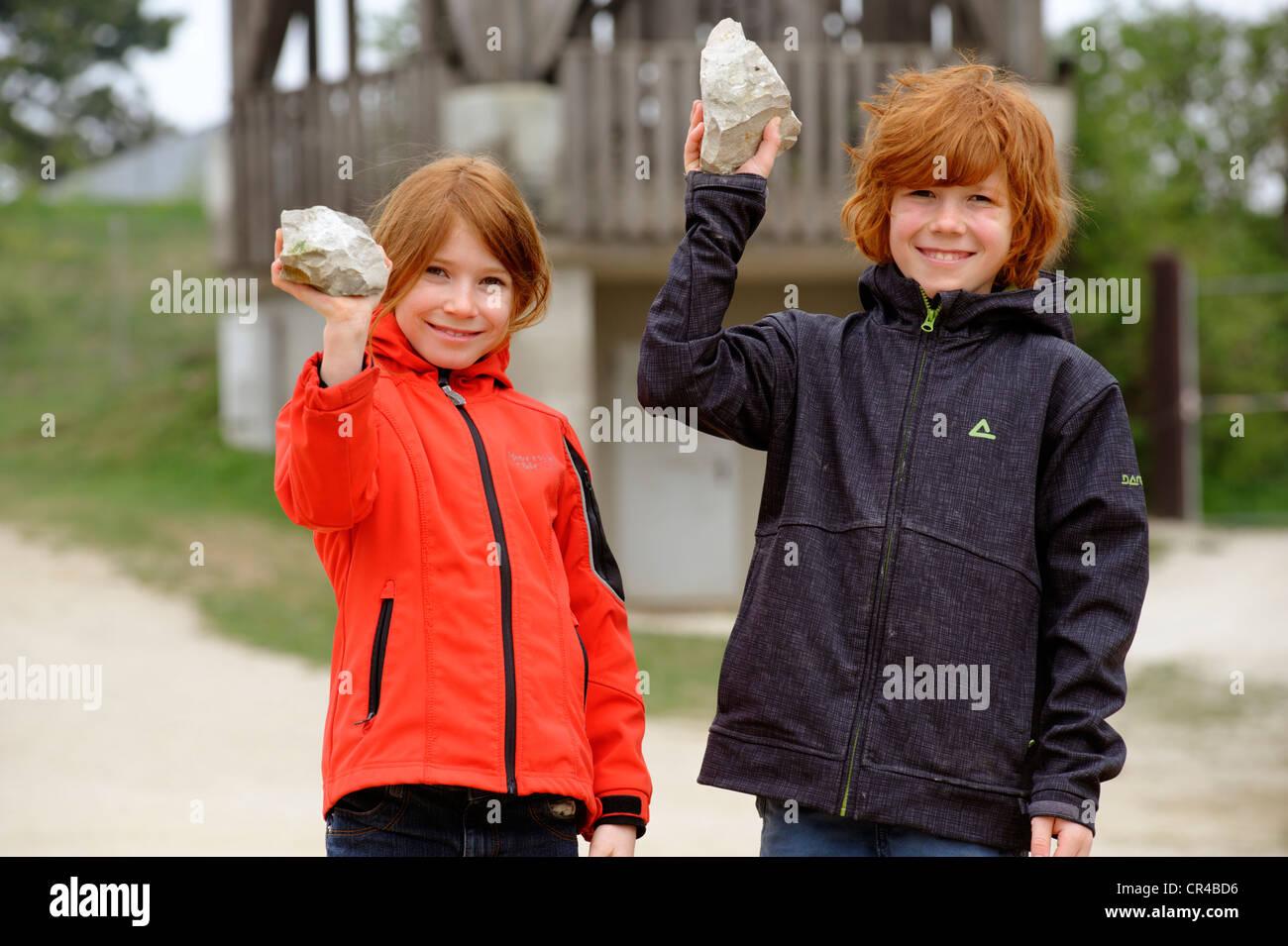 Deux enfants tenant des pierres contenant des fossiles de la rupture des roches en Hohenmirsberger Geozentrum Platte, Photo Stock