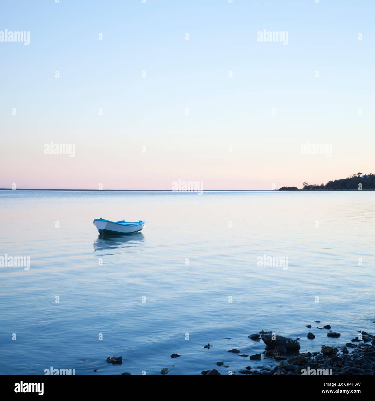 Petit bateau ancré sur de l'eau léchant doucement Photo Stock