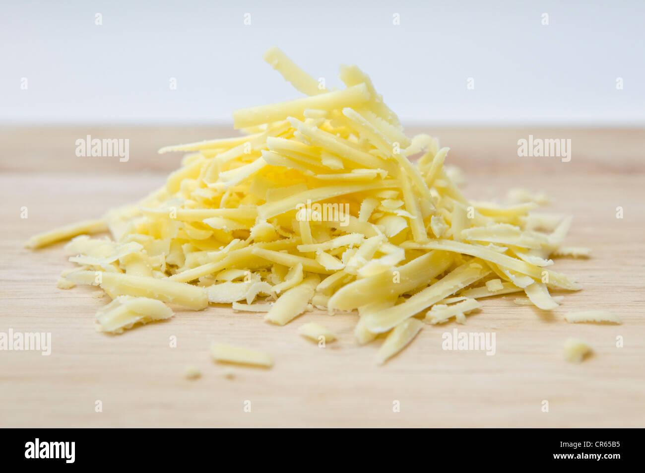 Fromage râpé sur planche en bois à l'arrière-plan blanc Photo Stock