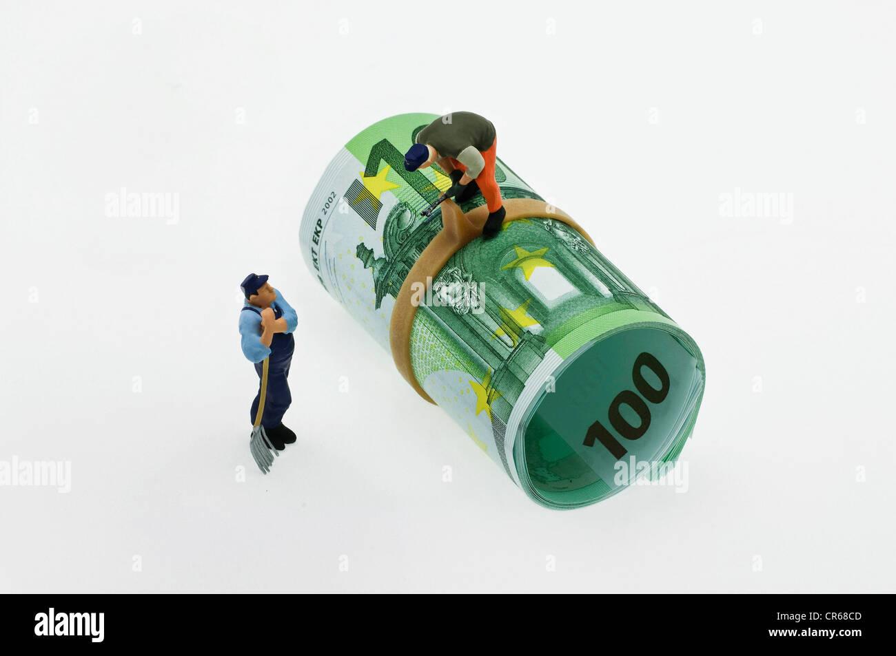 Deux figures miniatures d'ouvriers, l'un à l'aide d'un outil sur un rouleau de 100 euros, le Photo Stock