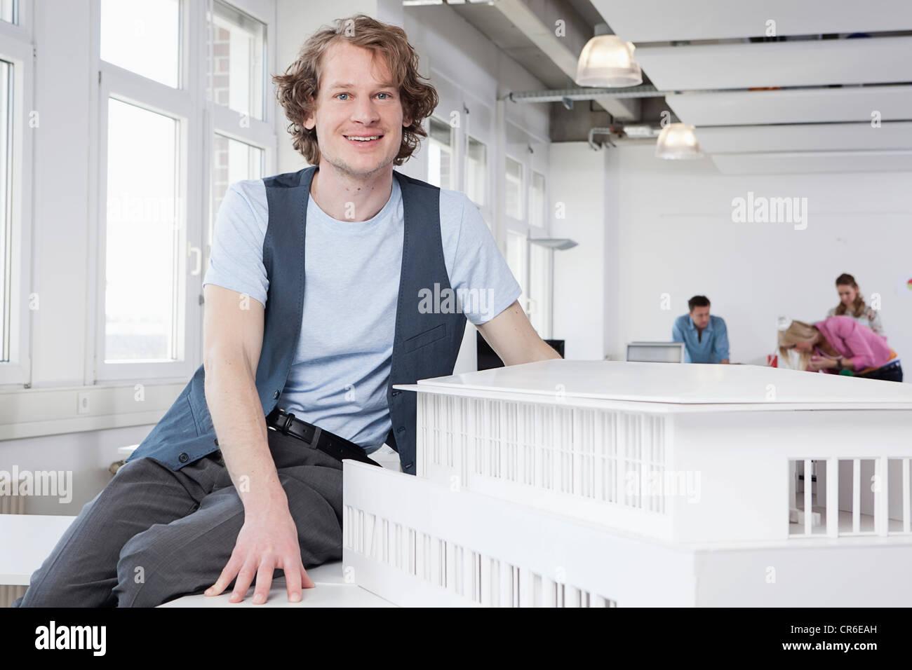 Germany, Bavaria, Munich, architecte avec modèle architectural, des collègues qui travaillent en arrière Photo Stock