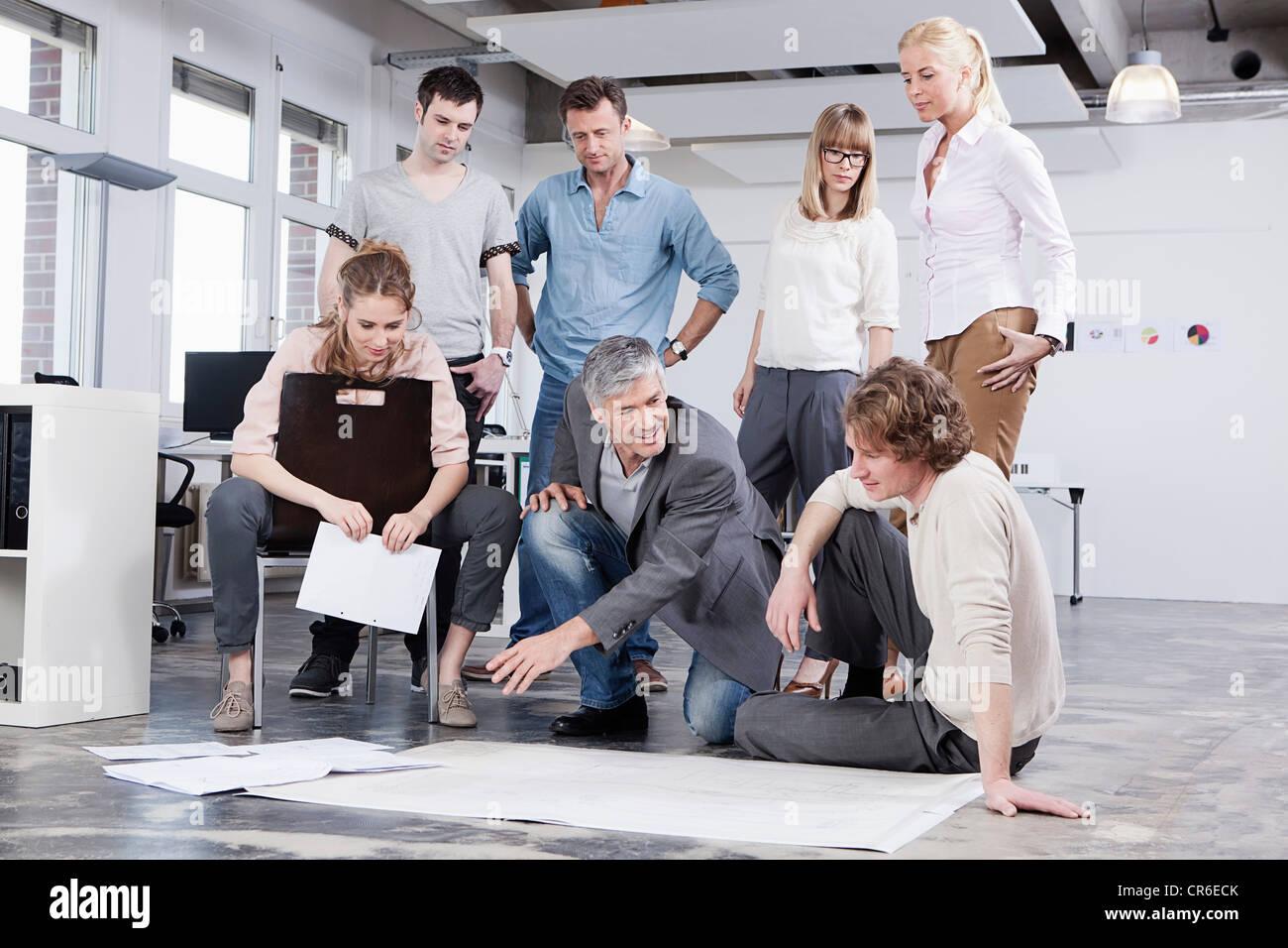 Germany, Bavaria, Munich, hommes et femmes discutant dans office Photo Stock