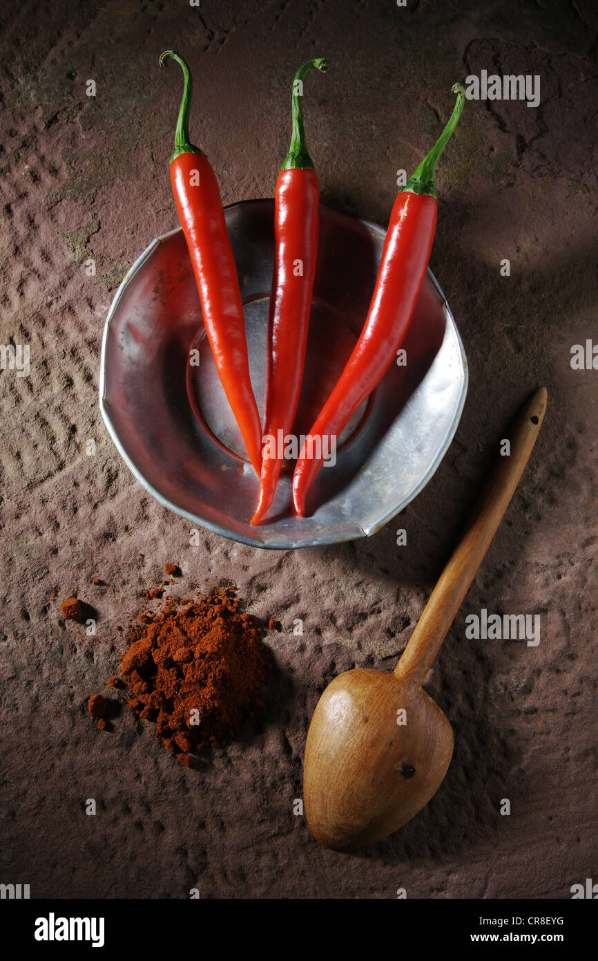 Trois piments forts (Capsicum) sur une plaque d'étain avec une cuillère en bois et la poudre de chili Photo Stock